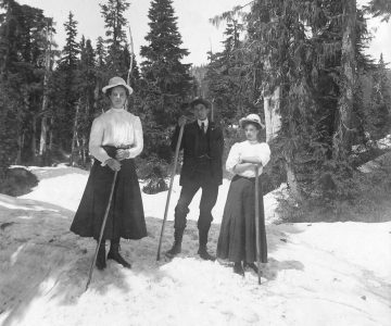 [Two women and a man holding walking sticks on snow]. CC-PH-04319.